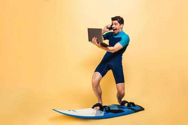 Возбужденный молодой человек на доске для серфинга разговаривает по телефону с помощью портативного компьютера.