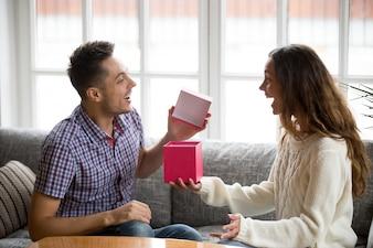 興奮している若い男が妻からプレゼントを受け取るギフトボックスを開く