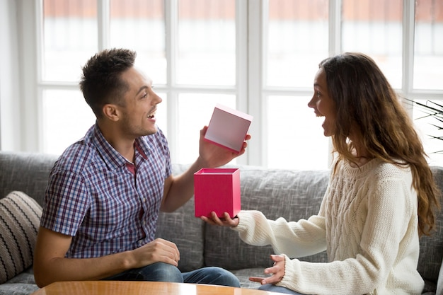 Excited young man opening gift box receiving present from wife