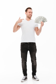 Excited young man pointing and holding money.