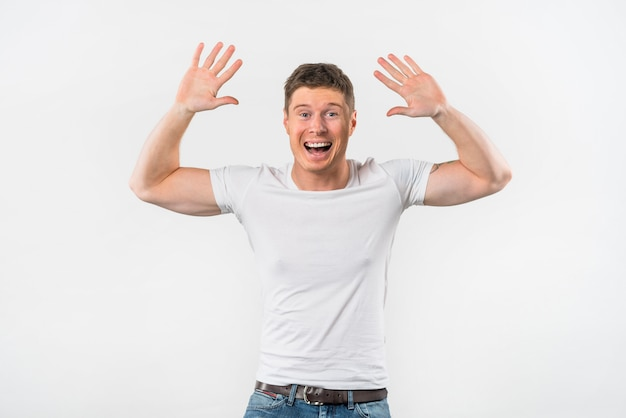Excited young man raising her arms to give high five against white backdrop