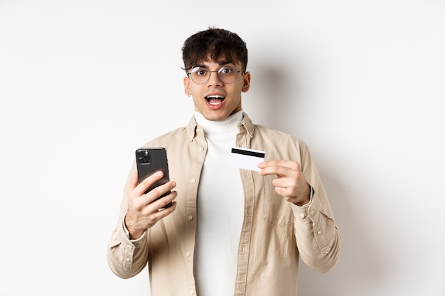 オンラインで買い物をし、携帯電話とプラスチックのクレジットカードを持って、インターネットで購入し、白い壁に立って興奮している若い男。