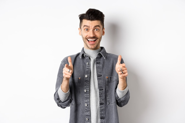 Excited young man showing thumbs-up and smiling happy, praise good thing, motivating you, recommending cool product, standing on white background.