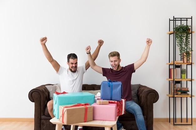 Eccitato giovane uomo seduto sul divano guardando scatole regalo colorato