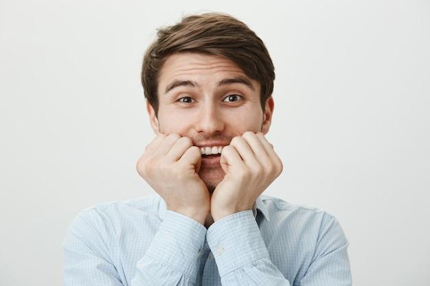 若い男が笑って興奮して、誘惑で顔に手をつないで