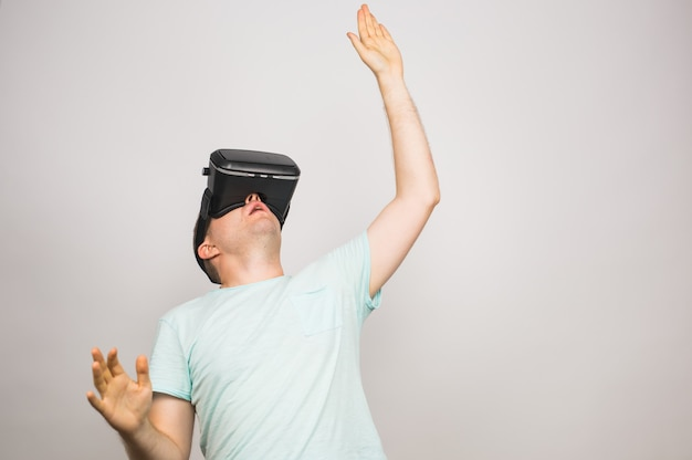 Vrヘッドセットを使用して灰色に分離された仮想現実を体験して興奮している若い男