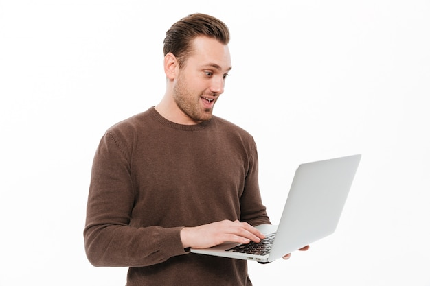 Excited young man using laptop computer.