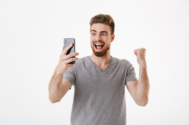 Excited young man using mobile phone make winner gesture.
