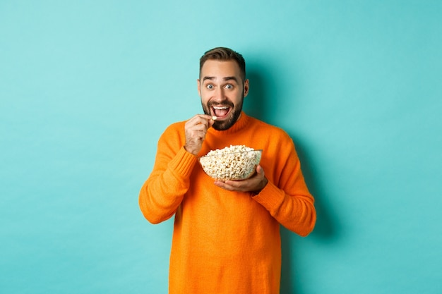 Excited young man watching interesting movie on tv screen, eating popcorn and looking amazed, blue background.
