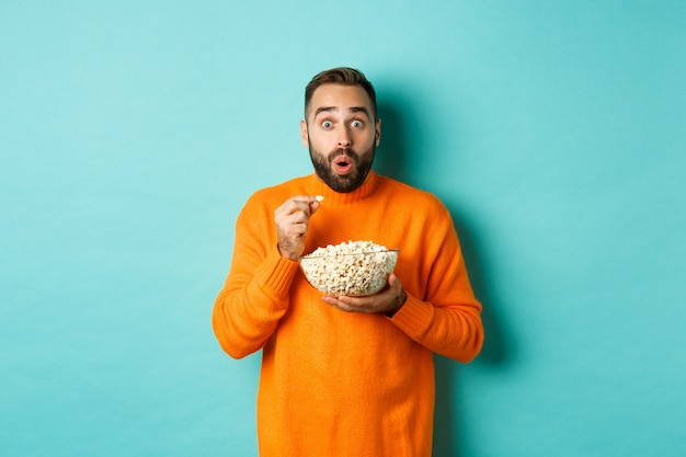 Excited young man watching interesting movie on tv screen, eating popcorn and looking amazed, blue background