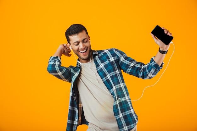 Взволнованный молодой человек в клетчатой рубашке стоит изолированно на оранжевом фоне и слушает музыку в наушниках и мобильном телефоне