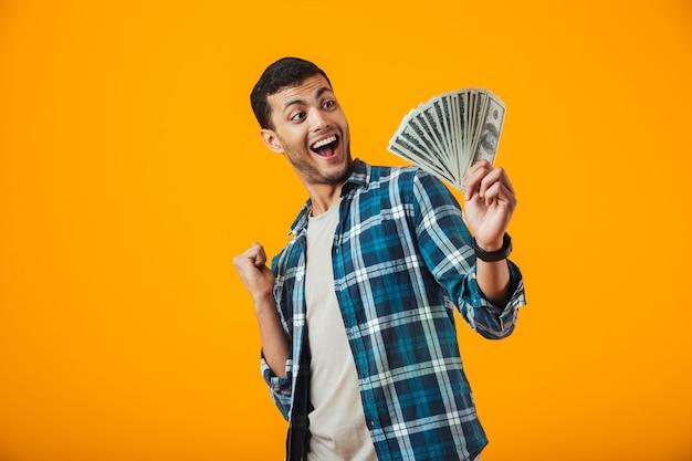 金色の紙幣を示すオレンジ色の背景に分離された格子縞のシャツ立っている身に着けている興奮の若い男