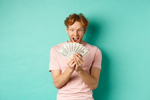 Excited young man winning prize money, counting cash and looking amazed at dollars, standing over turquoise background.