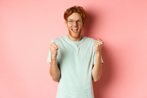 Excited young man winning prize, shouting with joy and triumph, making fist pump and saying yes, standing over pink background.