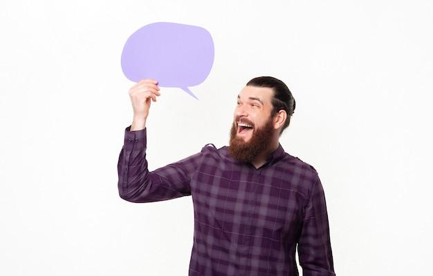 Возбужденный молодой человек с бородой смотрит на пустой речевой пузырь