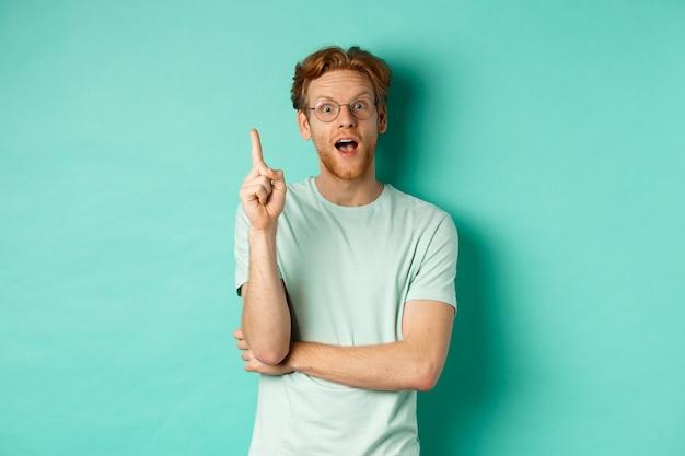 眼鏡の生姜髪、人差し指を上げる、アイデアを投げる、ミントの背景の上に立つ興奮した若い男