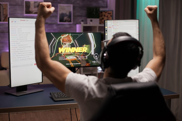 Excited young man with hands up after wining a competition of shooter games. esport streaming.