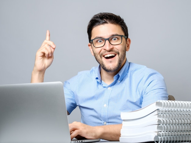 Excited young man with laptop pointing finger up