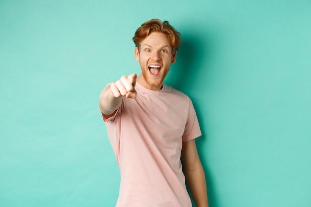 ターコイズブルーの背景の上に立って、カメラに指を向け、魅了されて微笑んで、何かクールなものをチェックしている赤い髪の興奮した若い男。