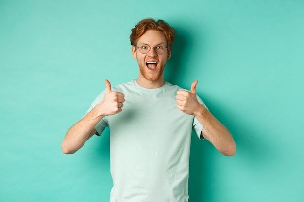 Возбужденный молодой человек с рыжими волосами, в очках, поднимающий вверх большие пальцы руки и согласный или хвалящий что-то, удивленный улыбающийся и говорящий «да», стоящий на бирюзовом фоне.