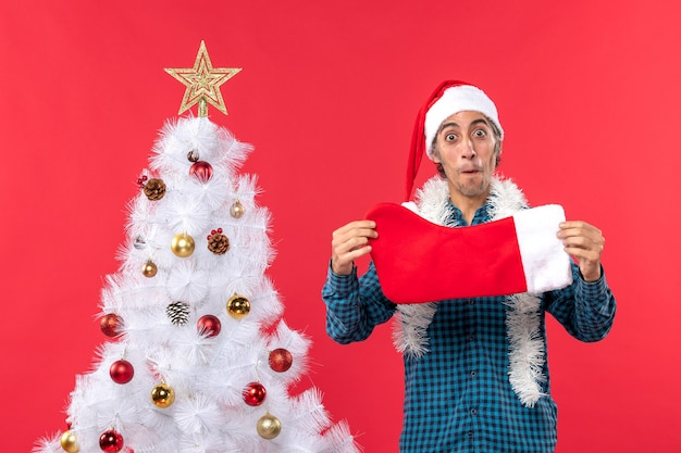 Excited young man with santa claus hat in a blue stripped shirt and holding christmas sock near xmas tree