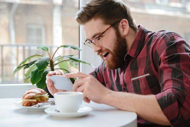 スマートフォンでカフェで昼食を撮影して興奮している若い男