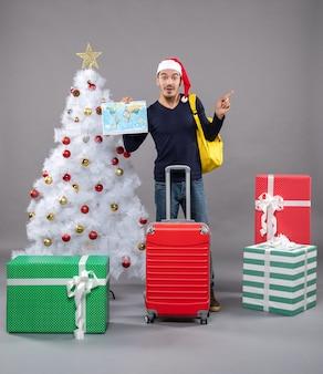 Возбужденный молодой человек с желтым рюкзаком держит карту возле белой рождественской елки на сером