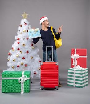 Возбужденный молодой человек с желтым рюкзаком держит карту возле елки на сером