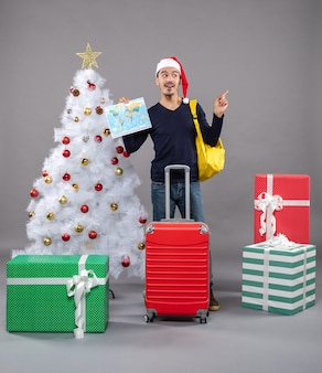 Возбужденный молодой человек с желтым рюкзаком держит карту на сером