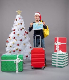 Возбужденный молодой человек с желтым рюкзаком держит карту обеими руками возле белой рождественской елки на сером