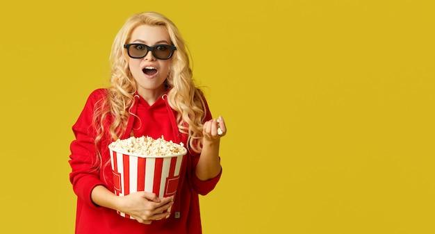 ポップコーンを食べる3 dメガネで興奮している若いモデルの女性は、映画に見えます。黄色の壁に分離
