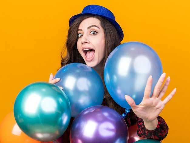 Excited young party girl wearing party hat standing behind balloons looking at camera showing empty hand isolated on orange wall