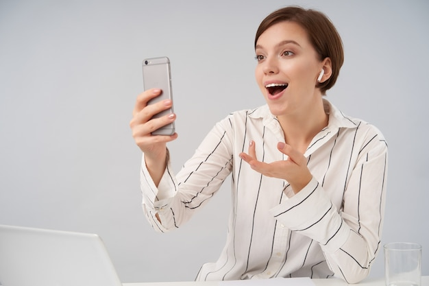 Excited young positive short haired brunette lady with casual hairstyle raising emotionally her palm and smiling widely while having video conversation with her mobile phone