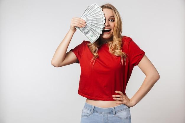 お金を保持している白い壁の壁の上に孤立してポーズをとって興奮している若いかなり美しい女性