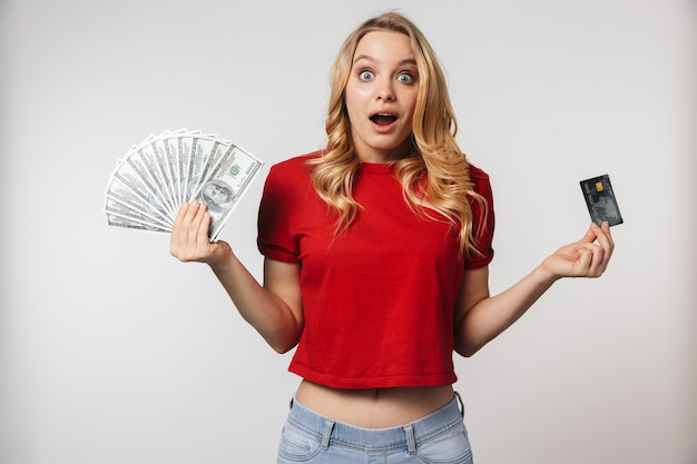 Excited young pretty beautiful woman posing isolated over white wall wall holding money and credit card