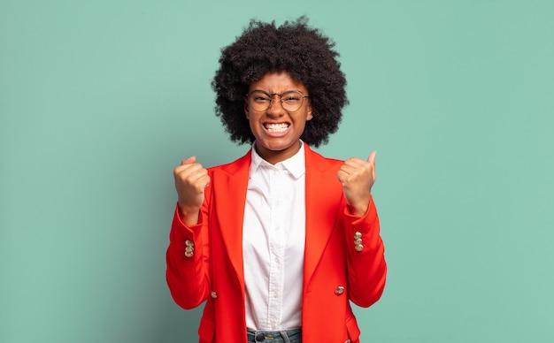 Возбужденная молодая красивая черная женщина, стиснув зубы