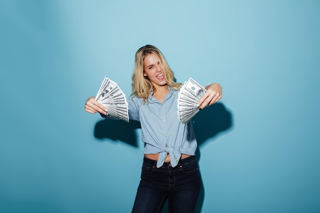 Excited young pretty blonde woman holding money in hands.
