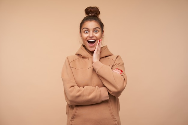 Excited young pretty brunette woman dressed in nude sweatshirt holding palm on her cheek while looking amazedly at front with wide eyes and mouth opened, isolated over beige wall
