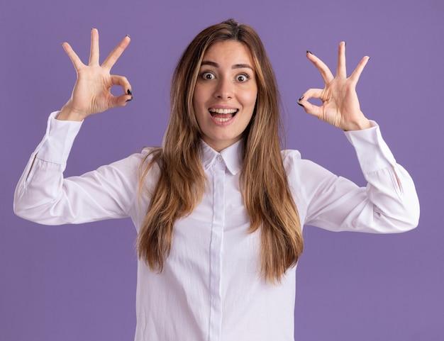 흥분된 젊은 백인 소녀는 복사 공간이 있는 보라색 벽에 격리된 두 손으로 확인 손 기호를 제스처합니다.