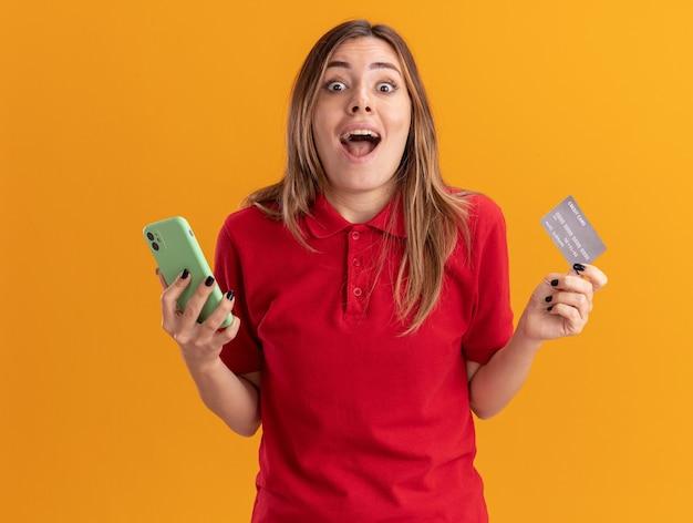 興奮した若いかなり白人の女の子はオレンジ色のクレジットカードと電話を保持します