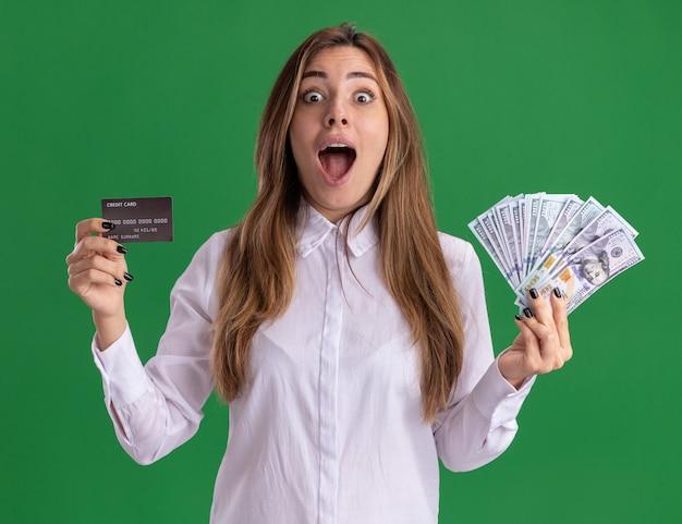 興奮した若いかなり白人の女の子は緑にお金とクレジットカードを保持します