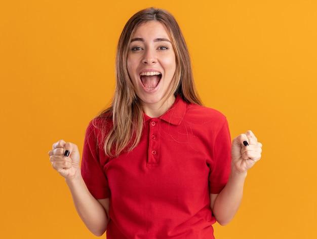 La giovane ragazza abbastanza caucasica emozionante tiene i pugni sull'arancia