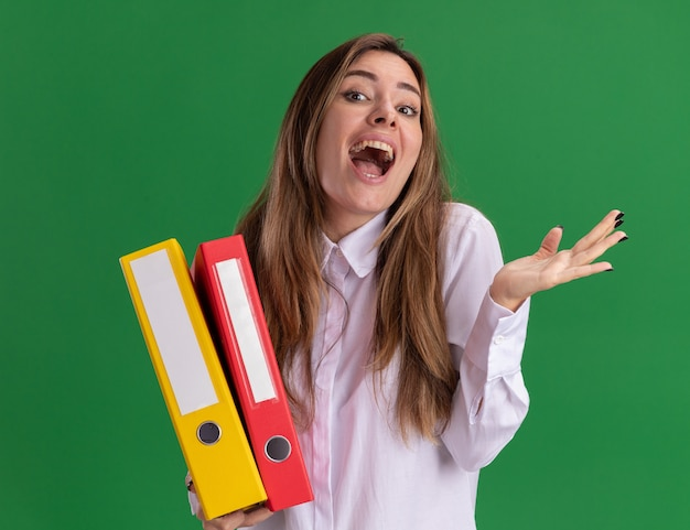 Excited young pretty caucasian girl keeps hand open and holds file folders on green