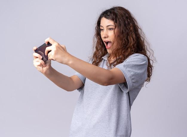 Возбужденная молодая симпатичная кавказская девушка, стоящая в профиле, держит мобильный телефон, играя в игру по телефону, изолированному на белой стене