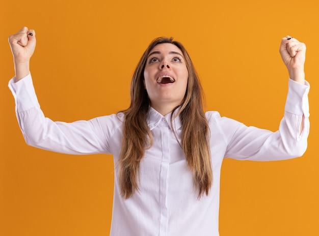 Возбужденная молодая симпатичная кавказская девушка стоит с поднятыми кулаками и смотрит вверх изолированно на оранжевой стене с копией пространства