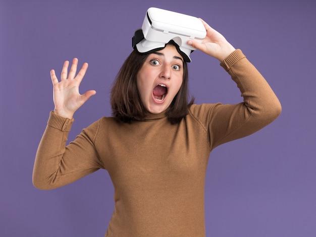 베레모 모자를 쓰고 vr 헤드셋을 들고 복사 공간이 있는 보라색 벽에 격리된 손을 들고 서 있는 흥분된 젊은 백인 소녀