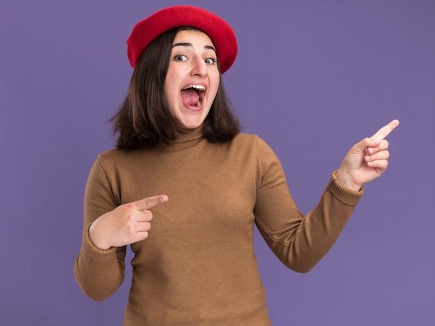 Eccitato giovane ragazza abbastanza caucasica con cappello berretto che punta a lato sulla porpora