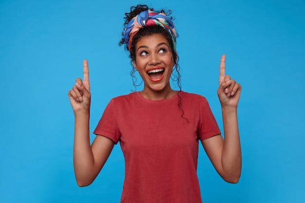 Eccitato giovane donna dai capelli scuri piuttosto ricci con acconciatura casual mantenendo la bocca spalancata mentre mostra verso l'alto con gli indici sollevati, in piedi su sfondo blu