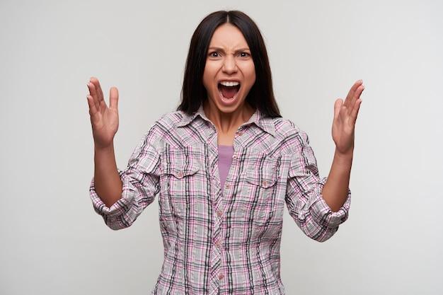 Eccitato giovane femmina dai capelli piuttosto scura con acconciatura casual guardando emotivamente con le mani alzate e tenendo la bocca spalancata, in piedi