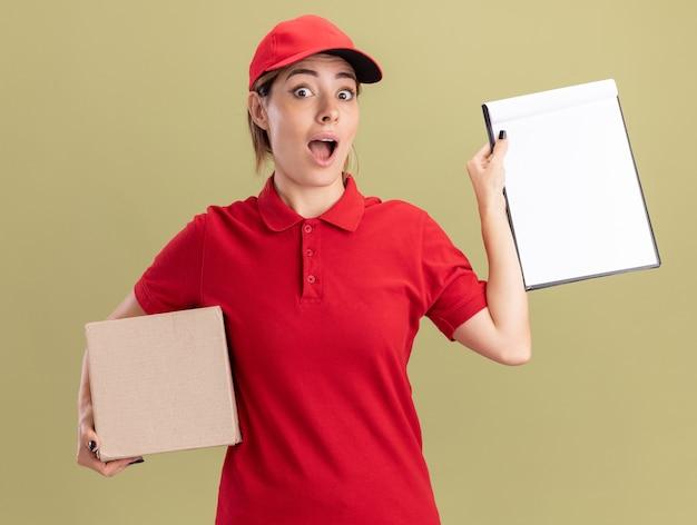 La giovane ragazza graziosa di consegna emozionante in uniforme tiene la lavagna per appunti e la scatola di cartone su verde oliva